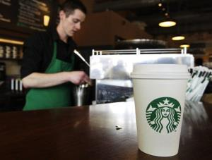 A Starbucks drink waits for a customer to pick it up as barista Josh Barrow prepares another at left, Friday, April 27, 2012, in Seattle.