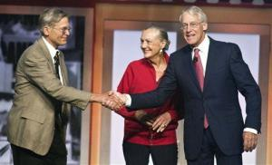 Jim Walton, left, Alice Walton, center, and Robson Walton, right, greet each other during the beginning of the Walmart shareholders meeting in Fayetteville, Ark., Friday, June 1, 2012.
