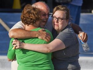 Tom Sullivan, center, embraces family members outside Gateway High School. He is searching for his son, who went to the movie.