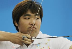 South Korean archer Im Dong-hyun lines up a shot during the men's team competition where he won gold at the Asian Games in Guangzhou, China, Monday, Nov. 22, 2010.