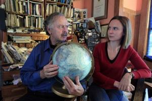 In this Friday, Oct. 28, 2011 photo, Richard Muller, left, and his daughter, Elizabeth Muller, hold a globe as they talk about their study on climate at their home in Berkeley, Calif.