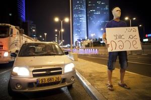 An Israeli man protests Israeli economic policies as others, not seen, block a highway in Tel Aviv on Sunday, July 15, 2012. The sign in Hebrew reads: Bibi you burned me too.