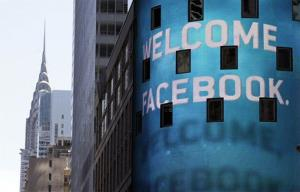 In this Friday, May 18, 2012 file photo, the animated facade of the Nasdaq MarketSite welcomes the Facebook IPO.