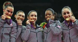 McKayla Maroney, Kyla Ross, Alexandra Raisman, Gabrielle Douglas, and Jordyn Wieber bite their gold medals at the women's gymnastics team final at the 2012 Summer Olympics, July 31, 2012, in London.