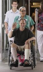 Shark bite victim Christopher Myers, of Denver, is wheeled out of Massachusetts General Hospital yesterday.