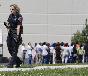 Police stand guard as bystanders watch at the scene of a shooting inside a Sikh temple in Oak Creek, Wis.