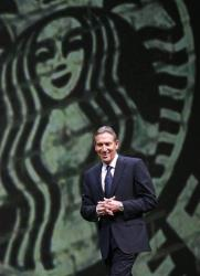Starbucks chairman and CEO Howard Schultz walks on stage to address the annual Starbucks shareholders meeting Wednesday, March 21, 2012, in Seattle.