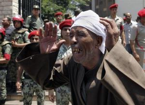 An Egyptian mourns outside the mosque at the funeral of 16 soldiers killed in an attack over the weekend by suspected militants in Sinai in Cairo, Egypt yesterday.