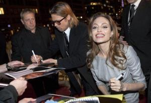 Angelina Jolie and Brad Pitt sign autographs as they arrive at the Cinema For Peace fund raising gala in Berlin Monday, Feb. 13, 2012.