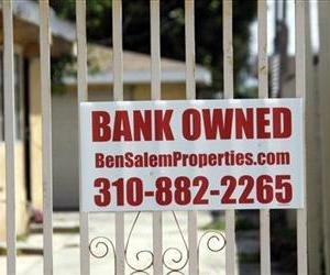 In this file photo taken July 21, 2010, a bank owned sign is seen on a home that is listed as a foreclosure on a HUD website, in Hawthorne, Calif.