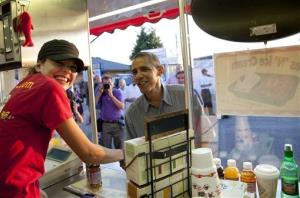 President Obama visits Cookie Smith at the CinnieSmiths mini cinnamon roll stand at the Iowa State Fair Monday.