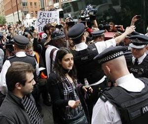 British police officers move the protesters in support of WikiLeaks founder Julian Assange from the front of the Ecuadorian Embassy in central London, Aug. 16, 2012.