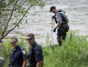 A police search dog unit searches the banks of the Credit River in Hewick Meadows Park in Mississauga, Ontario yesterday.
