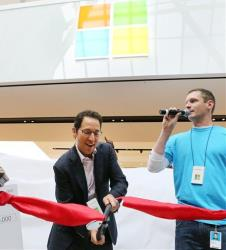 Chris Capossela, Chief Marketing Officer for Microsoft, left, cuts the ribbon, alongside Microsoft Store Manager Ty Hapworth, at the grand opening of a Boston Microsoft Store, Aug. 23, 2012.