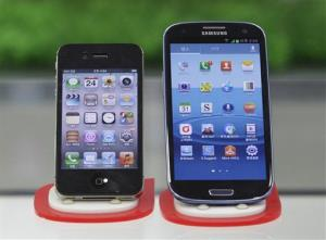Samsung Electronics' Galaxy S III, right, and Apple's iPhone 4S are displayed at a mobile phone shop in Seoul, South Korea, Friday.