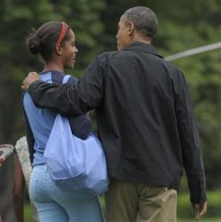 President Barack Obama puts his arm around daughter Malia as they and family friends walk to Marine One on the South Lawn of the White House.