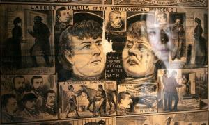 A member of staff is seen reflected in The Illustrated Police News on display during a press preview for the exhibition Jack the Ripper and the East End at the Museum in Docklands, London.