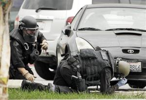 Los Angeles Police bomb squad members check for explosive devices outside a Bank of America branch in Los Angeles yesterday.
