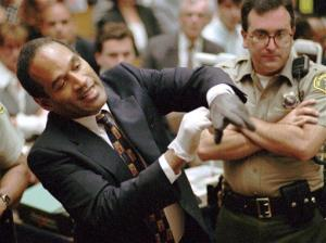 In this June 15, 1995, file photo, O.J. Simpson grimaces as he tries on one of the leather gloves prosecutors said he wore the night his ex-wife Nicole Brown Simpson and Ron Goldman were murdered.