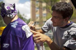 Minnesota Vikings kicker Chris Kluwe signs a fan's jersey in 2011.