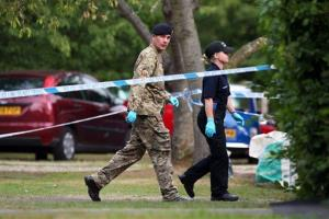 A member of the Royal Logistic Corps bomb disposal team walks with a police officer close to the home of murder victim Saad al-Hilli, in Claygate, England.