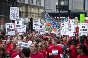 Thousands of public school teachers march on streets surrounding the Chicago Public Schools district headquarters yesterday.