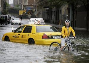 In this Aug. 28, 2011, file photo, a biker makes his way around a taxi stranded in floodwaters of Hurricane Irene, downgraded to a tropical storm, in New York.
