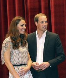 Prince William and his wife Kate, the Duke and Duchess of Cambridge, smile on stage following a performance at Rainbow Centre, a school for disabled children in Singapore, on Wednesday, Sept. 12, 2012.