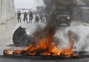 Afghan police stand by burning tires during a protest, in Kabul, Afghanistan, Monday, Sept. 17, 2012.
