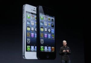 Apple CEO Tim Cook speaks in front of an image of the iPhone 5 during an Apple event in San Francisco, Wednesday, Sept. 12, 2012.