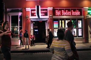 People walk past a strip club on Bourbon Street in the French Quarter section of New Orleans.