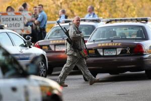 An officer walks through the area as police investigate a shooting at Accent Signage Systems on the north side of Minneapolis yesterday.