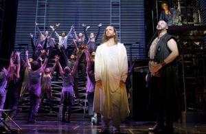 In this theater publicity image released by Boneau/Bryan-Brown, Paul Nolan, and Lee Siegel, right, are shown with the cast during a performance of Jesus Christ Superstar, in New York.