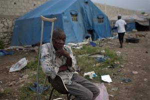 Rezilhome Diverne, 68, sits outside his tent at a camp for people displaced by the 2010 earthquake after the passing of Tropical Storm Isaac in Port-au-Prince, Haiti, Monday Aug. 27, 2012.
