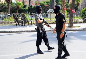 Elite police officers patrol in front of the French embassy, partially seen in background, Friday, Sept.21, 2012 in Tunis.
