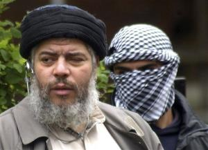 This Friday, April 30, 2004 file photo shows Muslim cleric Abu Hamza al-Masri, as he arrives with a masked bodyguard outside the closed Finsbury Park Mosque in London.