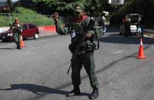 Members of the Bolivarian militia, a militia created by President Hugo Chavez estimated to number more than 100,000 who do not report to the armed forces, stand at a checkpoint in the 23 de Enero neighborhood of Caracas, Venezuela, Saturday, Oct. 6, 2012.  Chavez is running for re-election against...