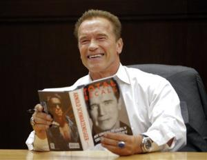 Arnold Schwarzenegger holds his book Total Recall during a book signing event at a Barnes & Noble store in Los Angeles, Friday, Oct. 5, 2012.