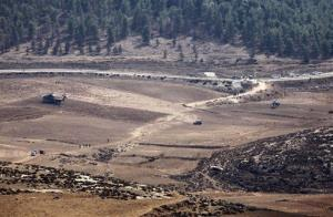 Israeli Army vehicles and helicopters are seen in an open area as they search for the remains of a drone in the Negev southern Israel, Saturday, Oct. 6, 2012.