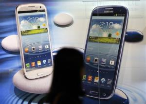 A woman walks by a billboard of Samsung Electronics's smartphones in Seoul, South Korea, Friday, Oct. 5, 2012.