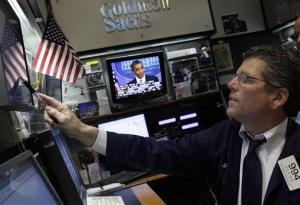 President Obama is visible on a television screen as a trader checks his screens in the Goldman Sachs booth on the floor of the New York Stock Exchange.