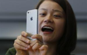 A customer tries on her new iPhone 5 at the Apple store in Hong Kong Friday, Sept. 21, 2012.