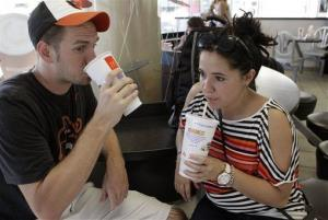 Luke Husemann, and Christina Nunez of Baltimore sip on extra-large soft drinks at a fast-food restaurant in New York, Thursday, Sept. 13, 2012.