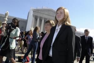 Abigail Fisher, right, who sued the University of Texas, walks outside the Supreme Court in Washington, Wednesday, Oct. 10, 2012.