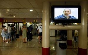 People line up to check with migration officials before departing at the Jose Marti International airport in Havana, Cuba, next to a screen showing Fidel Castro.