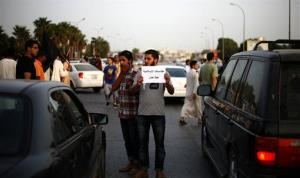 A Libyan follower of Ansar al-Sharia Brigades carries a placard reads in Arabic our Islamic holies are red line, during a protest in front of the Tibesti Hotel, in Benghazi, Libya, Sept. 14, 2012.