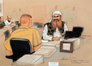 Khalid Sheikh Mohammed speaks with his lawyer while wearing a camouflage vest during Military Commissions pretrial hearings against the five Gitmo prisoners accused of the Sept. 11 terrorist attacks.