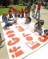 Kountze High School cheerleaders and other children work on a large sign in Kountze, Texas.