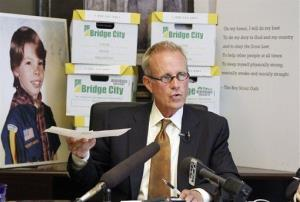 In this June 14, 2012, file photo, attorney Kelly Clark speaks in front of former court case illustrations and boxes full of records from the Boy Scouts of America in Portland, Ore.