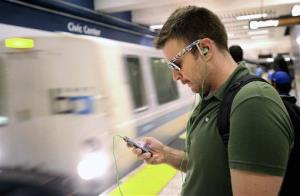 A commuter checks his cell phone while waiting for a BART train at San Francisco's Civic Center station.